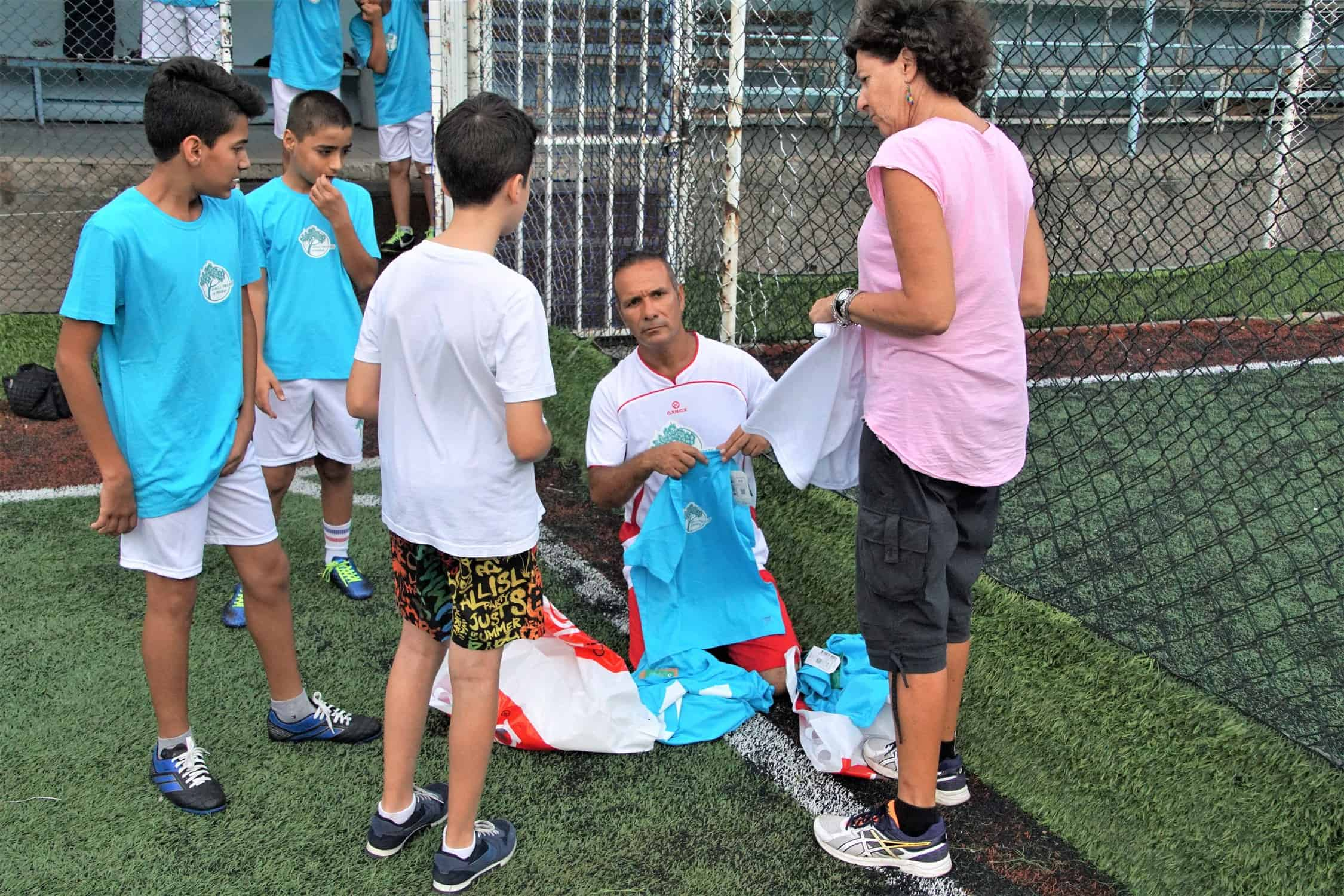 ahmad-julie-giving-football-tshirts-refugee-childfen